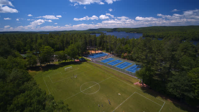 aerial view of summer camp grounds where children are sailing and playing a variety of sports - recreational horse riding stock videos & royalty-free footage