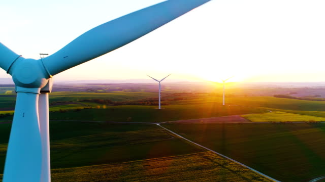 Aerial view of summer countryside with wind turbines and agricultural fields 4K