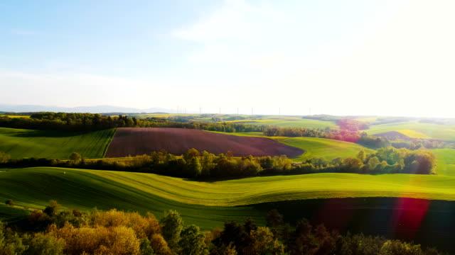 Luchtfoto van zomer landschap met windturbines en landbouwgronden.