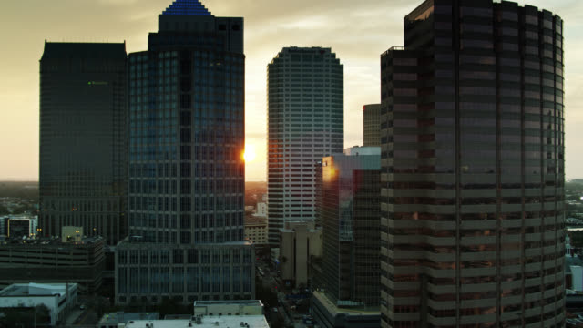 aerial view of sun setting behind downtown tampa skyscrapers - real time stock videos & royalty-free footage