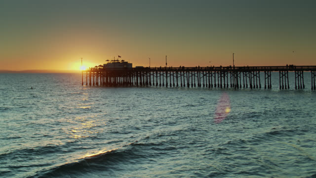 aerial view of sun setting behind newport beach pier with catalina island in distance - channel islands california stock videos & royalty-free footage