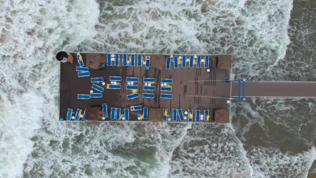 aerial view of sunbeds on a wharf in a beach during stormy weather - rectangle stock videos & royalty-free footage