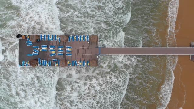 stockvideo's en b-roll-footage met luchtfoto van ligbedden op een kade in een strand tijdens stormy weather - pier