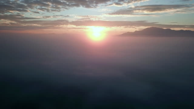 aerial view of sunrise above the cloud and mountain range - stratosphere stock videos & royalty-free footage