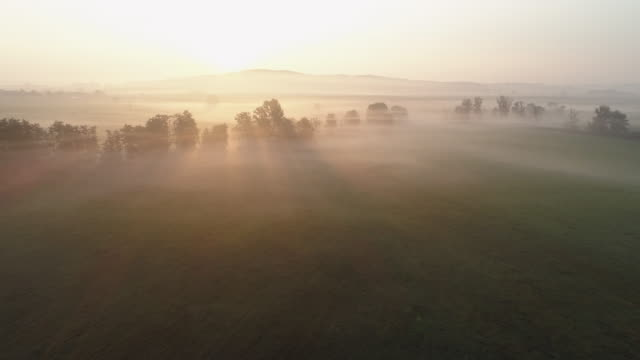 aerial view of sunrise over foggy landscape with the river altmühl near the source. franconia, bavaria, germany. - nebel stock-videos und b-roll-filmmaterial
