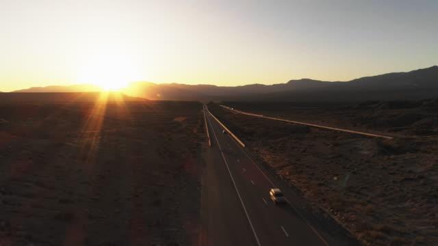 早期の春に、近くの高原メスキート、ネバダ州、アメリカ、ハイランドのテーブルの山の間の高速道路上の日の出の空中ビュー。車やトラックのわずかなトラフィック。 静的カメラでドロー - ネバダ州点の映像素材/bロール