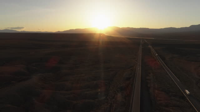 早期の春に、近くの高原メスキート、ネバダ州、アメリカ、ハイランドのテーブルの山の間の高速道路上の日の出の空中ビュー。車やトラックのわずかなトラフィック。カメラの動きをパン� - ネバダ州点の映像素材/bロール