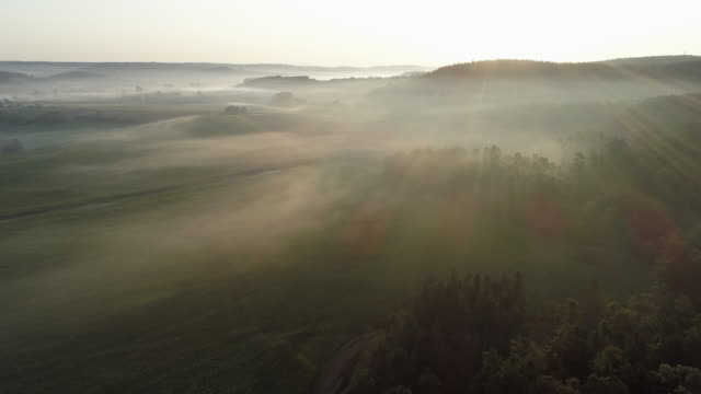 stockvideo's en b-roll-footage met aerial view of sunrise with foggy rural landscape. franconia, bavaria, germany. - schemering
