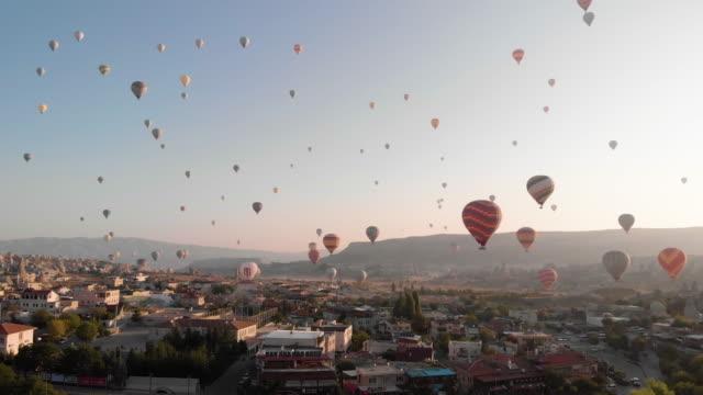 vídeos de stock, filmes e b-roll de vista aérea do nascer do sol com os balões de ar quente que voam sobre a paisagem icónica - capadócia