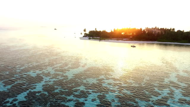 vídeos de stock, filmes e b-roll de vista aérea do pôr do sol sobre uma ilha maldivas - vazante