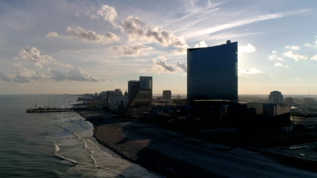 aerial view of sunset over atlantic city boardwalk and casinos in new jersey - atlantic city stock-videos und b-roll-filmmaterial