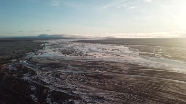 aerial view of sunset over frozen glacial rivers in iceland - area selvatica video stock e b–roll