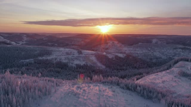 aerial view of sunset over snow covered forest in winter - 30 seconds or greater stock videos & royalty-free footage