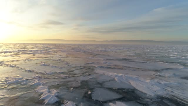 aerial view of sunset over the frozen baikal lake in winter, russia - russland stock-videos und b-roll-filmmaterial