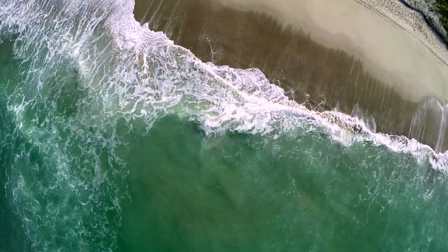 Aerial view of surf sweeping across sandy beach
