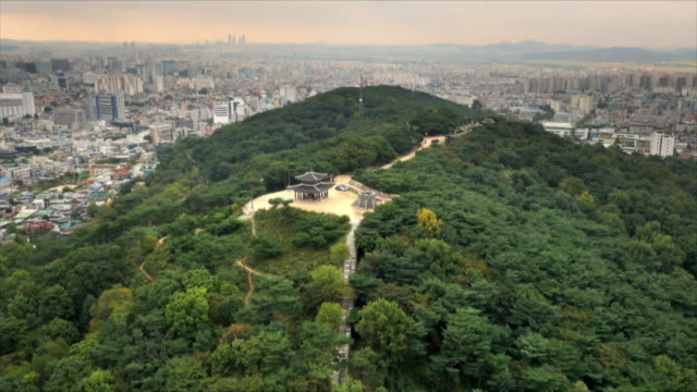 aerial view of suwon hwaseong fortress on mountain and suwon cityscape in the background - korea stock-videos und b-roll-filmmaterial