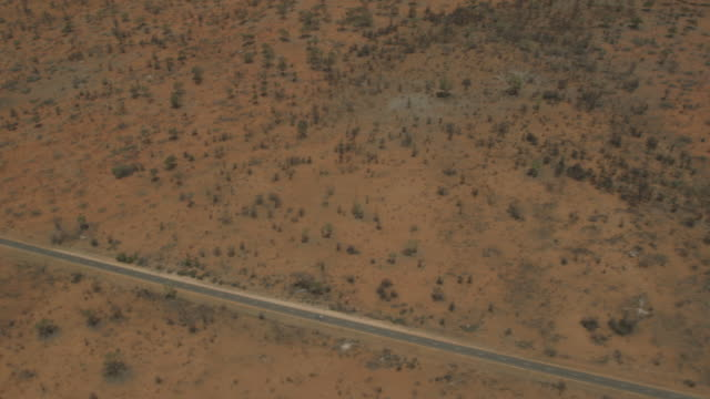 vídeos de stock e filmes b-roll de aerial view of tarmacked outback road, nt - eternidade