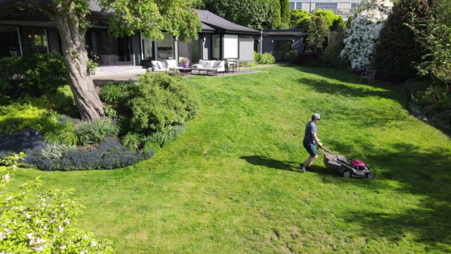 aerial view of teenage boy mowing grass in backyard on summer afternoon - one teenage boy only stock videos & royalty-free footage