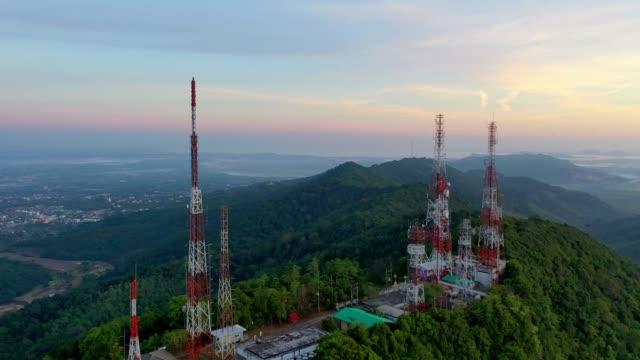 vídeos de stock, filmes e b-roll de vista aérea de antenas da tevê do mastro da telecomunicação no nascer do sol na montanha sobre a cidade - flutuar no ar