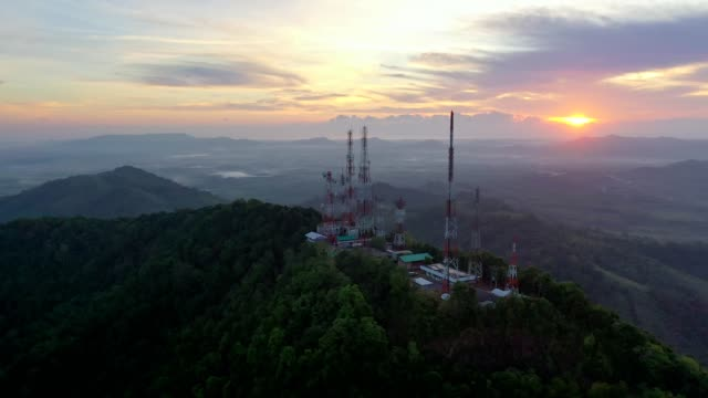 aerial view of telecommunication mast tv antennas at sunrise on mountain over the city - communications tower stock videos & royalty-free footage