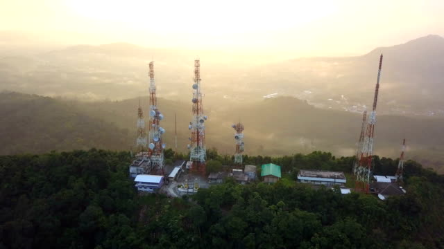aerial view of telecommunication mast tv antennas at sunrise on mountain over the city - microwave stock videos & royalty-free footage