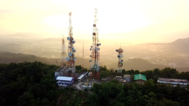 aerial view of telecommunication mast tv antennas at sunrise on mountain over the city - radio stock videos & royalty-free footage
