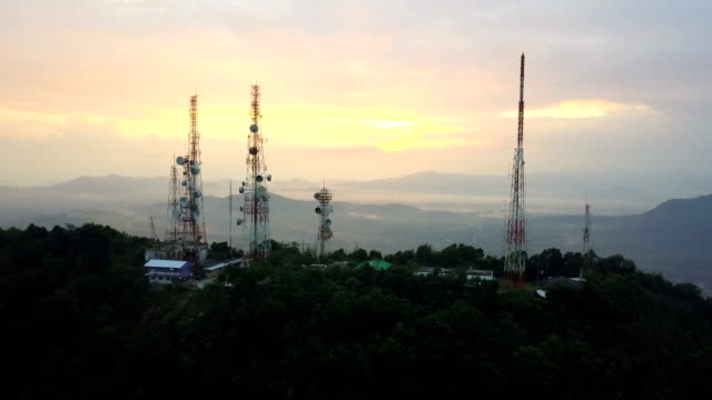 Luchtfoto van telecommunicatie mast TV antennes bij zonsopgang op de berg boven de stad