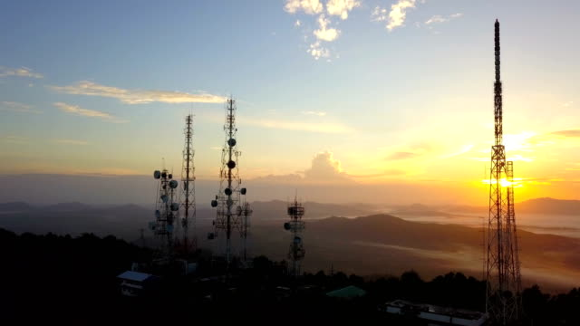 aerial view of telecommunication mast tv antennas at sunrise on mountain over the city - portability stock videos & royalty-free footage