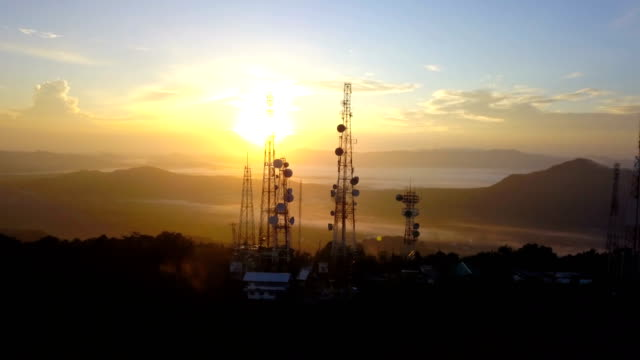 aerial view of telecommunication mast tv antennas at sunrise on mountain over the city - frequency stock videos & royalty-free footage