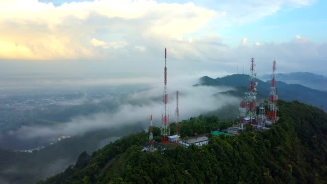 aerial view of telecommunication mast tv antennas with fog in the city - telecommunications equipment stock videos & royalty-free footage