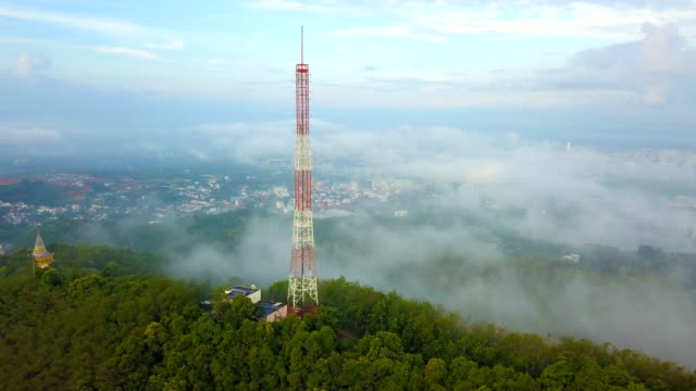 Aerial view of Telecommunication mast TV antennas with fog in the city