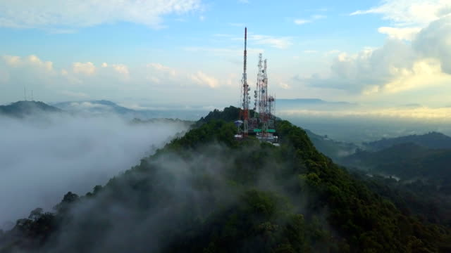 aerial view of telecommunication mast tv antennas with foggy on mountain over the city - microwave stock videos & royalty-free footage