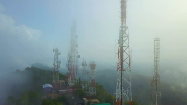 aerial view of telecommunication mast tv antennas with foggy on mountain over the city - telecommunications equipment stock videos & royalty-free footage