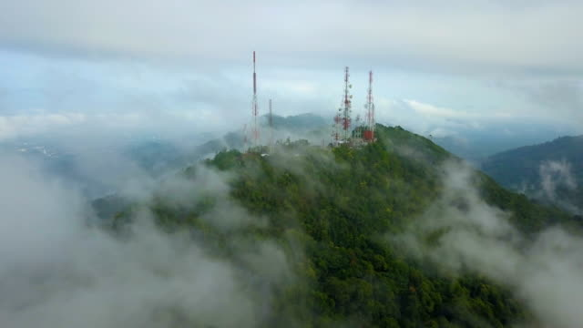 vídeos y material grabado en eventos de stock de vista aérea de antenas de telecomunicación mástil tv con niebla en la montaña sobre la ciudad - antena aparato de telecomunicación