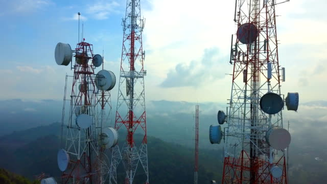 aerial view of telecommunication mast tv antennas with foggy on mountain over the city - global communications video stock e b–roll