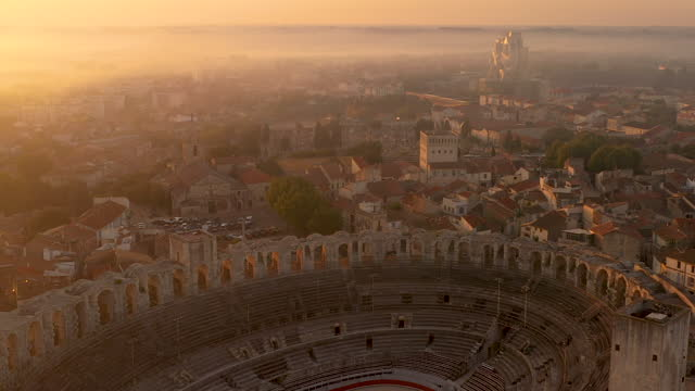 aerial view of the arles amphitheatre at sunrise, once a thriving place during the roman empire. - amphitheater stock videos & royalty-free footage