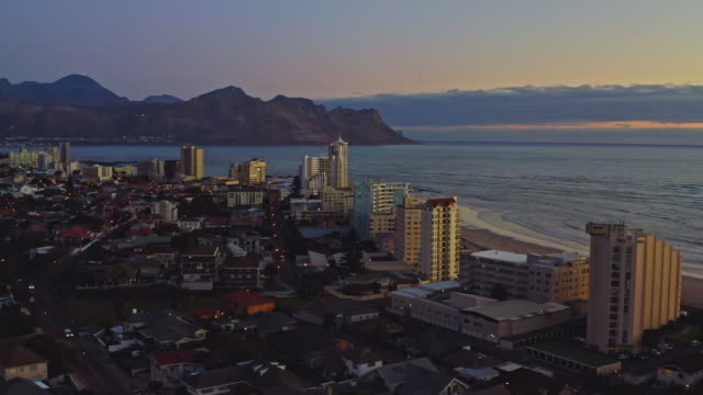 aerial view of the beach at strand, cape town at dusk - città del capo video stock e b–roll