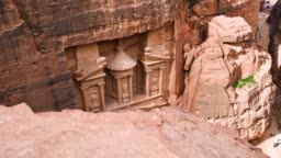 Aerial view of the beautiful Al Khazneh (The Treasury) with tourists admiring it from below. Petra is a historical and archaeological city in southern Jordan.