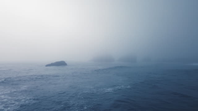 stockvideo's en b-roll-footage met aerial view of the blue ocean, calm waves and protruding cliffs in a very dense fog (ariya's beach, oregon, usa) - oregon amerikaanse staat
