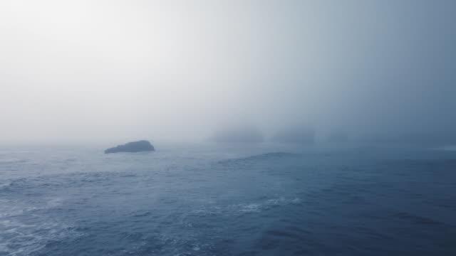 aerial view of the blue ocean, calm waves and protruding cliffs in a very dense fog (ariya's beach, oregon, usa) - oregon stato usa video stock e b–roll