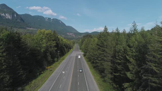 vidéos et rushes de vue aérienne de l'autoroute 2 occupée dans la forêt entre les montagnes voisines de gold bar, état de washington. vidéo de drone avec le mouvement ascendant de caméra. - nord ouest américain