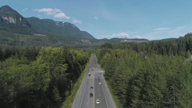 vidéos et rushes de vue aérienne de l'autoroute 2 occupée dans la forêt entre les montagnes voisines de gold bar, état de washington. vidéo de drone avec la caméra statique. - nord ouest américain