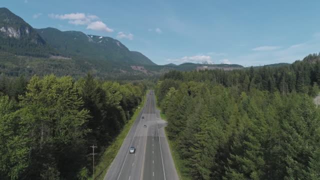 vidéos et rushes de vue aérienne de l'autoroute 2 occupée dans la forêt entre les montagnes voisines de gold bar, état de washington. vidéo de drone avec le mouvement avant et ascendant de caméra. - nord ouest américain