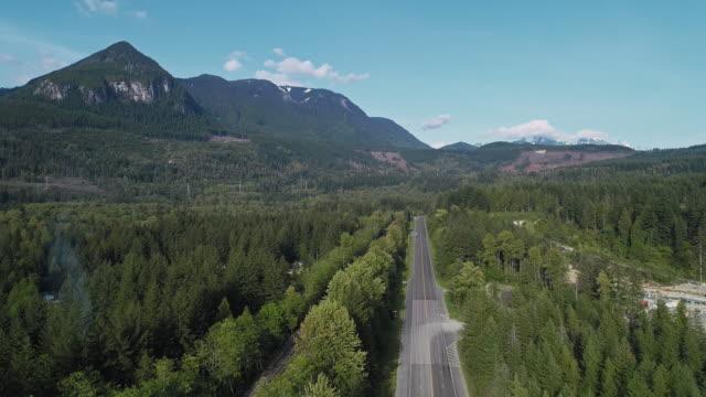 vidéos et rushes de vue aérienne de l'autoroute 2 occupée dans la forêt entre les montagnes voisines de gold bar, état de washington. vidéo de drone avec le mouvement descendant de caméra. - nord ouest américain