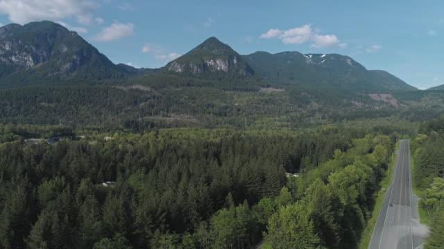 vidéos et rushes de vue aérienne de l'autoroute 2 très fréquentée dans la forêt entre les montagnes voisines de gold bar, état de washington. vidéo de drone avec le mouvement ascendant de la caméra. - nord ouest américain