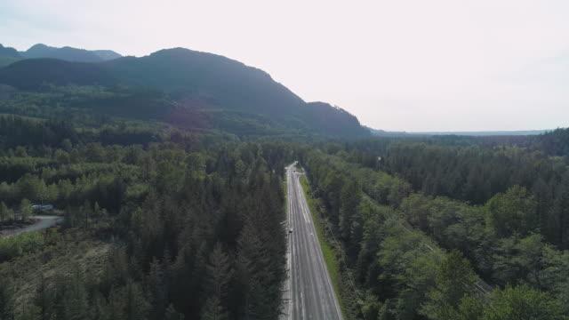 vidéos et rushes de vue aérienne de l'autoroute 2 très fréquentée dans la forêt entre les montagnes voisines de gold bar, état de washington. vidéo de drone avec le mouvement de la caméra avant. - nord ouest américain