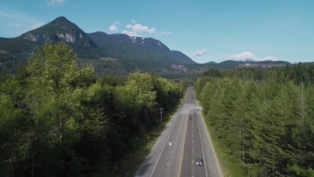 vidéos et rushes de vue aérienne de l'autoroute 2 très fréquentée dans la forêt entre les montagnes voisines de gold bar, état de washington. vidéo de drone avec le mouvement descendant de la caméra. - nord ouest américain