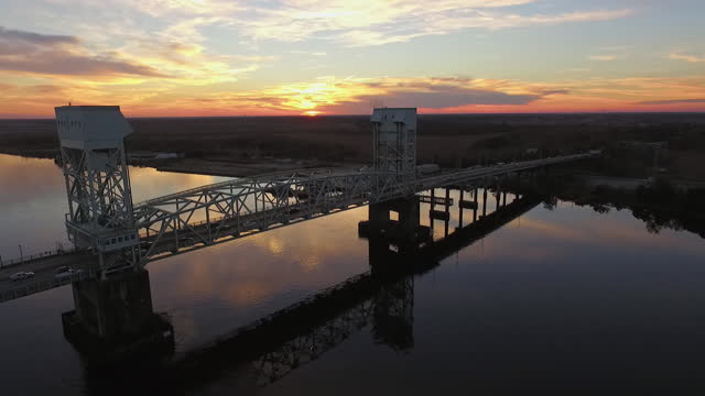 drone. aerial view of the cape fear memorial bridge as cars drive over and murmurations of birds fly around during majestic sunset - wilmington north carolina stock-videos und b-roll-filmmaterial