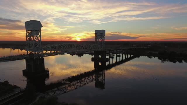 stockvideo's en b-roll-footage met drone. aerial view of the cape fear memorial bridge as cars drive over during majestic sunset - wilmington north carolina