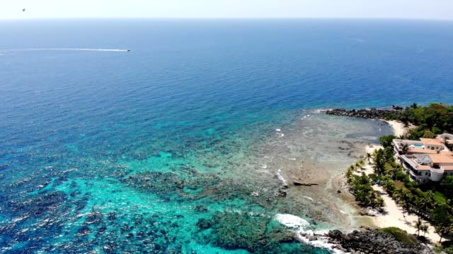 Aerial view of the clear water coast with a boat in the background in West End Honduras